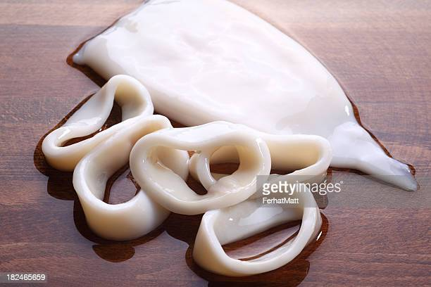 raw calamari rings on wooden table - matt calamari stock photos and pictures