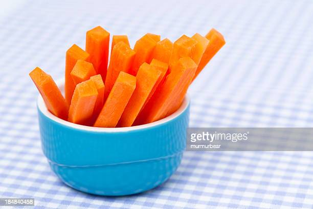 Raw carrot sticks inside of a blue ceramic bowl