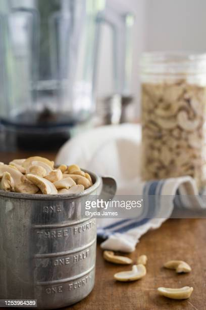 raw cashews in a vintage measuring cup - brycia james stock pictures, royalty-free photos & images