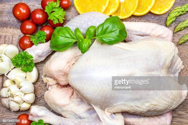 raw chicken on chopping board with vegetables and spicy - huhn geflügelfleisch stock-fotos und bilder