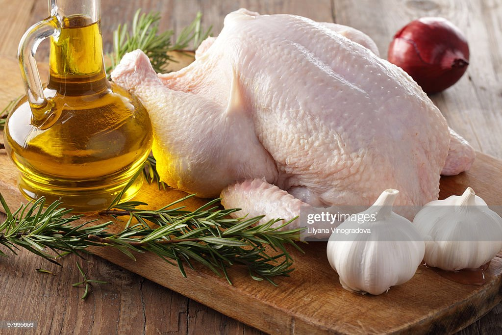 Raw chicken with rosemary, garlic, and olive oil : Stock Photo