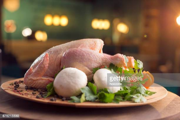 Raw chicken with vegetables on wooden plate