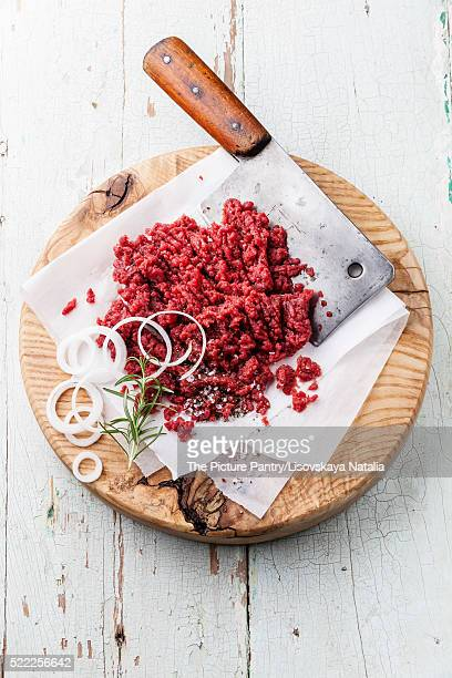 Raw chopped meat and meat cleaver on wooden cutting board on blu
