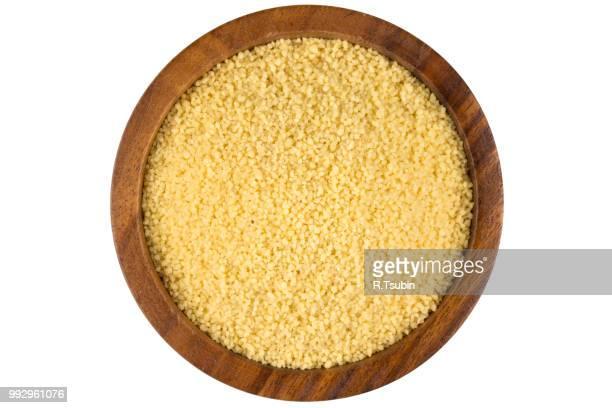 raw couscous in a wooden bowl on white background - couscous photos et images de collection