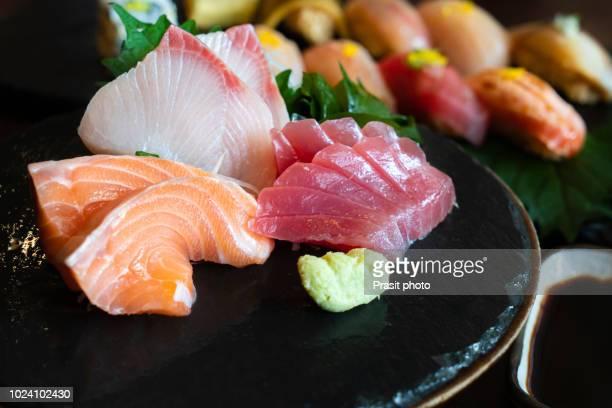 raw fish sashimi traditional japanese food set includes raw salmon, raw tuna, raw yellow tail (hamachi) sliced with sliced radish and vegetable - sashimi fotografías e imágenes de stock
