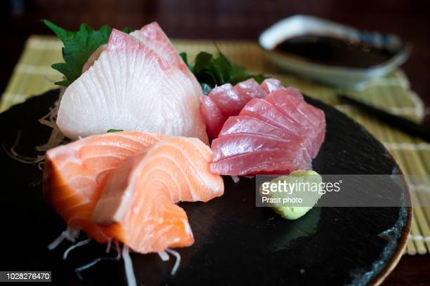 raw fish sashimi traditional japanese food set includes raw salmon, raw tuna, raw yellow tail (hamachi) sliced with sliced radish and vegetable - wasabi stock pictures, royalty-free photos & images