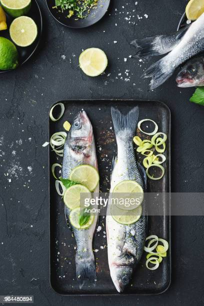 raw fish with lime and herbs on a baking tray - dolphin fish stock pictures, royalty-free photos & images