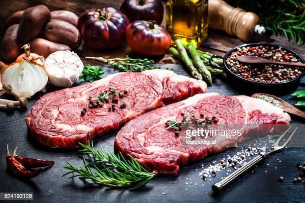 Raw fresh beef steak fillets on dark background