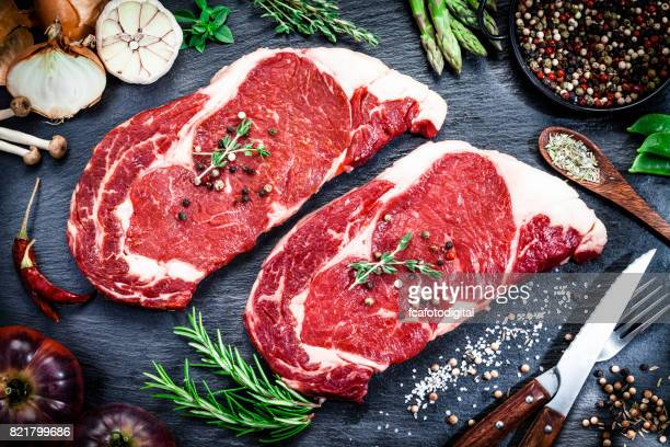 raw fresh beef steak on dark background - meat stock pictures, royalty-free photos & images