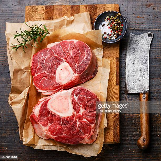 Raw fresh cross cut veal shank and seasonings for making Osso Buco on wooden cutting board with meat cleaver
