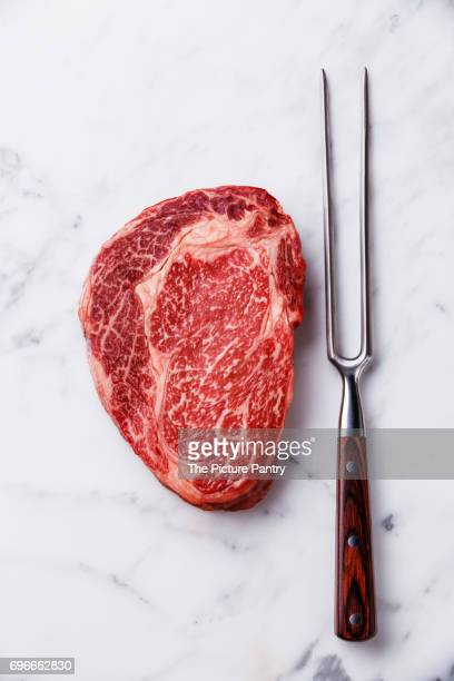 Raw fresh marbled meat Steak Ribeye Black Angus and meat fork on white marble background copy space