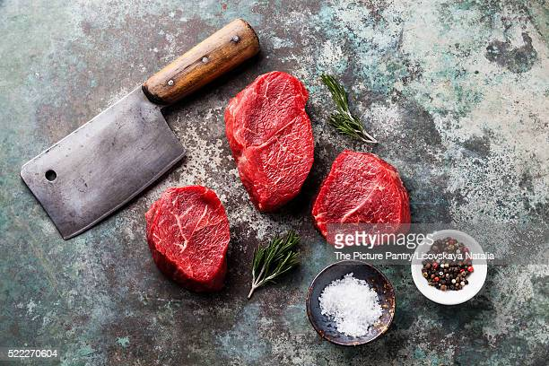 Raw fresh marbled meat Steak, seasonings and meat cleaver on metal background