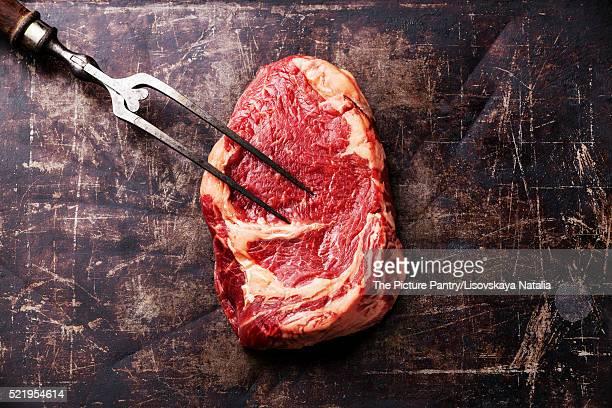 Raw fresh meat Ribeye Steak and meat fork on dark metal backgrou