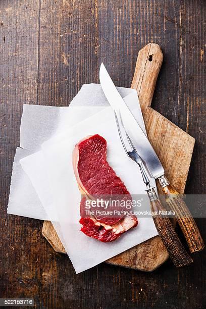 Raw fresh meat Ribeye steak entrecote on cutting board on dark w