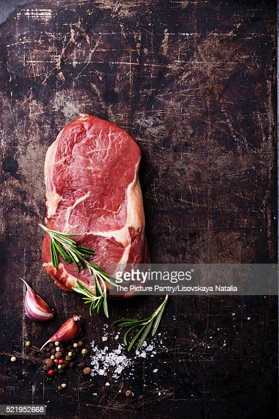 Raw fresh meat Steak Ribeye and seasonings on dark metal backgro