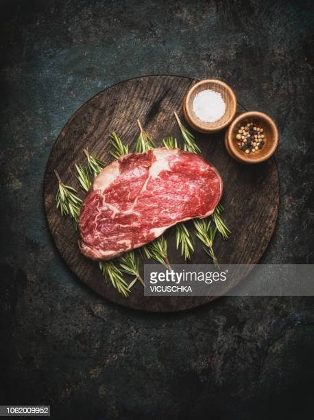 raw fresh meat steak with herbs and spices on round cutting board - meat stock pictures, royalty-free photos & images