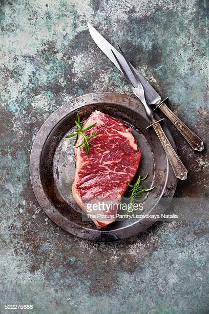 Raw fresh meat Striploin Steak and carving set on metal background