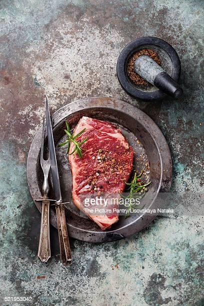 Raw fresh meat Striploin steak and seasoning on metal background