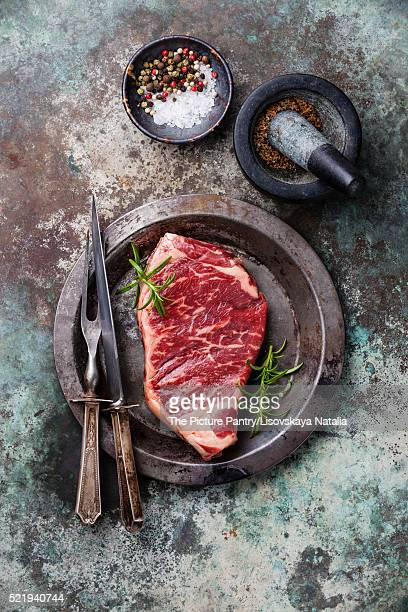 Raw fresh meat Striploin Steak and spices in mortar on metal background