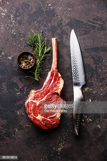 Raw fresh meat Veal rib Steak on bone and kitchen knife on dark background