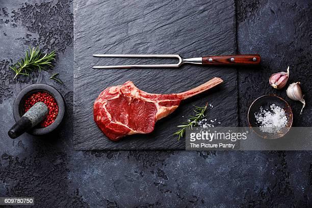 Raw fresh meat Veal rib Steak on bone and seasonings on dark background