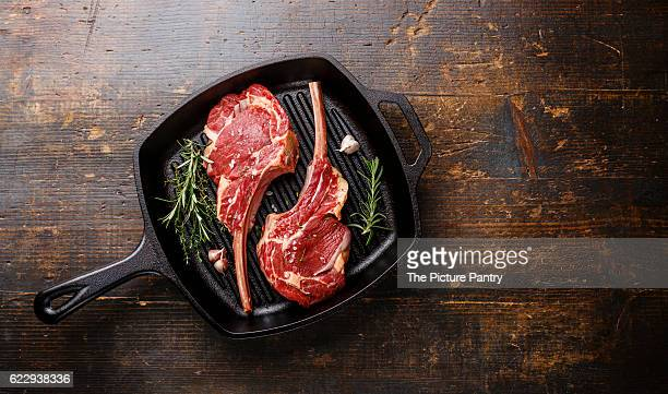 Raw fresh meat Veal ribs on frying Grill pan on wooden background copy space