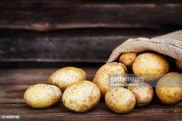 raw fresh potatoes in the sack on wooden background - raw potato stock pictures, royalty-free photos & images