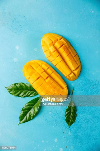 Raw fresh sliced mango on blue background