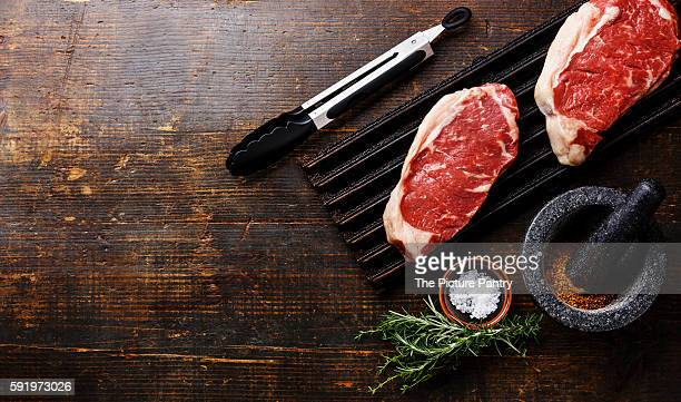Raw fresh Steak Striploin on black cast iron grill and spices in mortar on wooden background