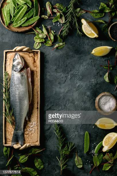 Raw fresh uncooked fish sea bass on ceramit plate ready to cook with lemon. Sea salt. Black and green beans. Green salad as frame over dark texture...