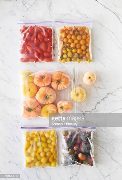 raw frozen tomatoes in plastic bags on marble - aliment surgelé photos et images de collection