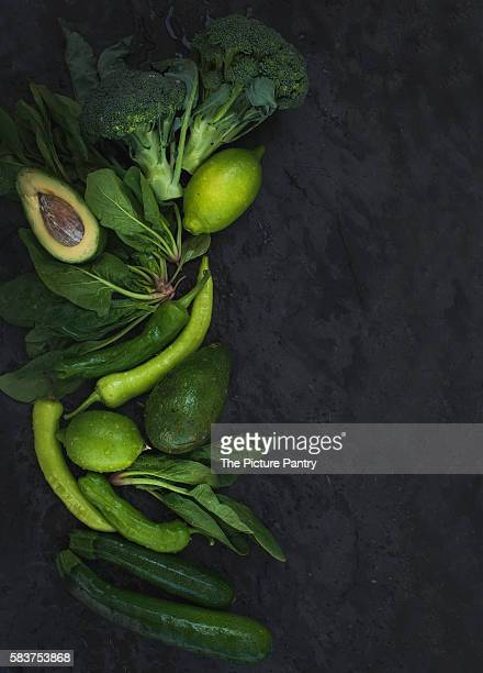 Raw green vegetables set. Broccoli, avocado, pepper, spinach, zucchini and lime on  dark stone background