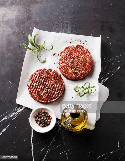 Raw Ground beef meat Burger steak cutlets on dark marble background