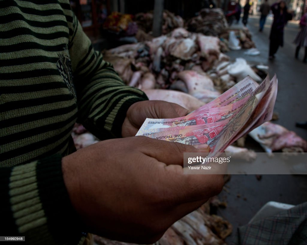 Raw hide and skin dealer holds money on October 30, 2012 in Srinagar, the summer capital of Indian administered Kashmir, India. Muslim countries produce the highest number of raw hides during the Eid ul Adha (Feast of the Sacrifice). With the Sacrificing of animals on the eve of Eid, millions of raw hides, mostly from sheep, goat and other bovine animals are prepared. The trade generates billions of dollars drives the raw material need of the footwear industry, where most of the hides are utilized after tanning. The State of Jammu and Kashmir, a Muslim majority state, also produces three million hides from different animals annually, with some two hundred thousand hides made ready on Eid. The hides are mostly exported in raw form to India based tanneries which process it to leather that is mostly exported to Europe.