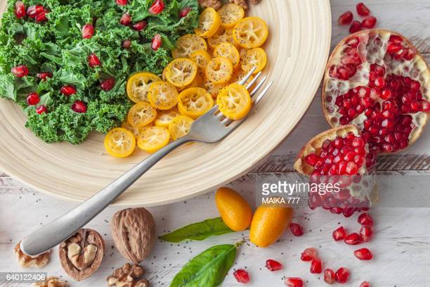 Raw kale salad with pomegranate, kumquat and wallnut