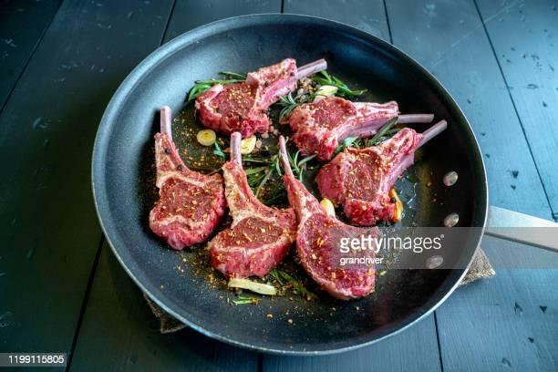 côtelettes d'agneau crues dans un skillet prêt à être cuit avec de l'ail, des poireaux et du romarin comme assaisonnement - côtelette photos et images de collection
