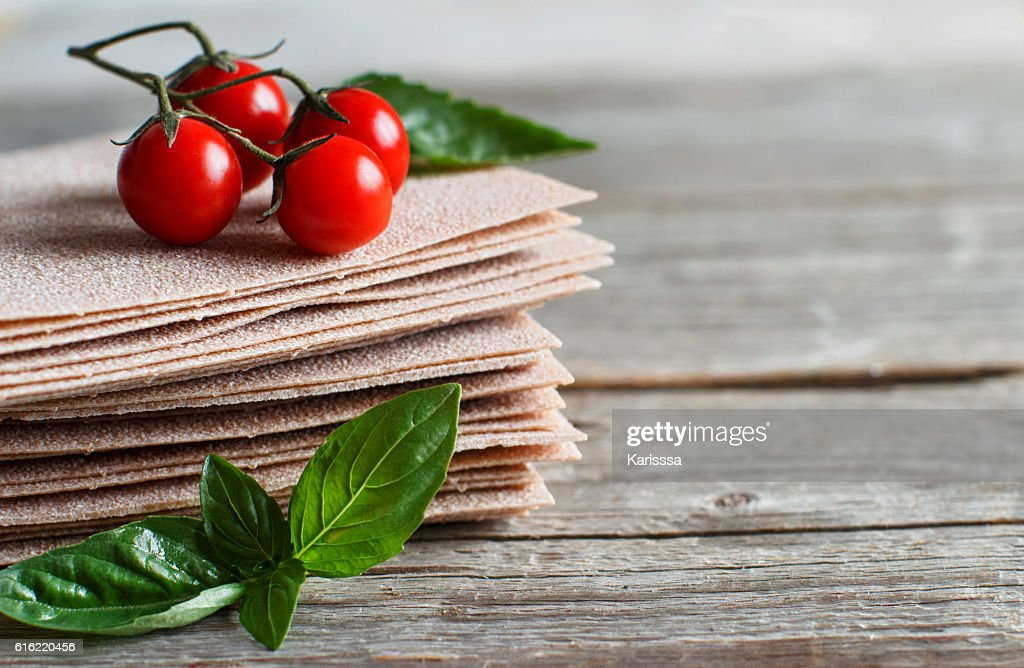 Raw lasagna sheets,basil and cherry tomatoes : Stock-Foto