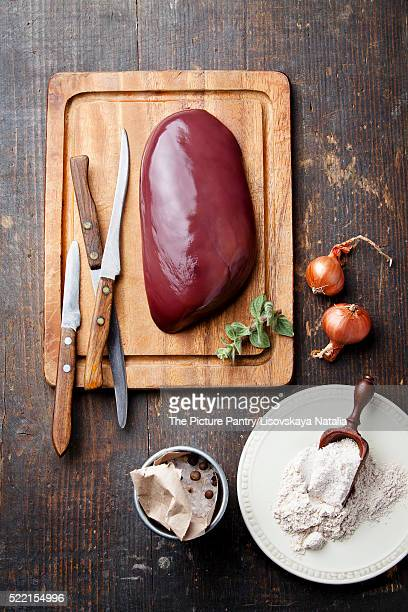 Raw liver with ingredients on wooden textured table