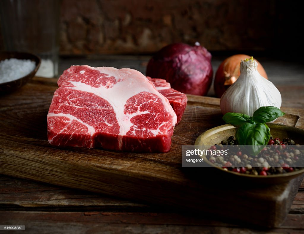 Raw marbled beef on a cutting board, onion, garlic, spices : Stock Photo