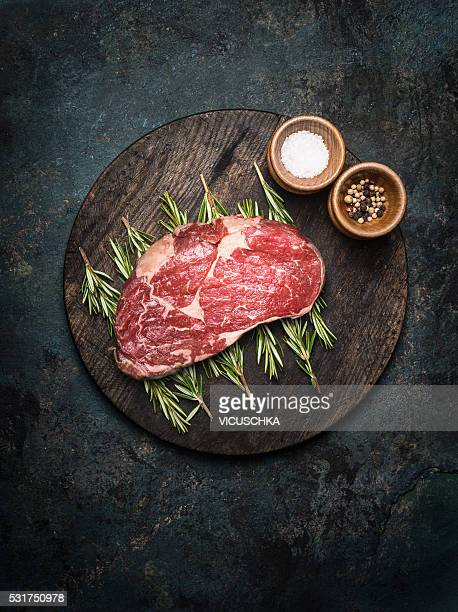 Raw marbled meat Steak on rosemary branches and wooden gutting board