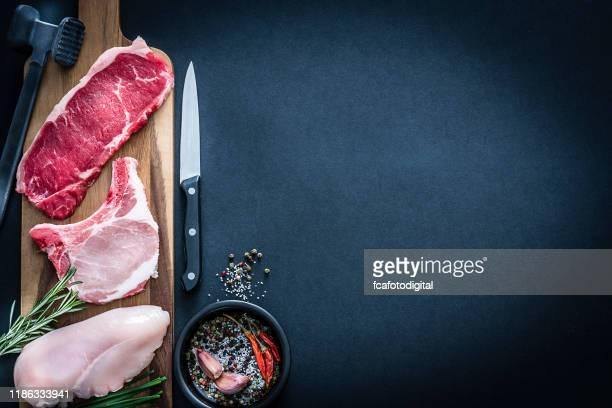 assortiment de viande crue - boeuf, poulet et côtelettes de porc abattus d'en haut sur fond sombre - porc viande photos et images de collection