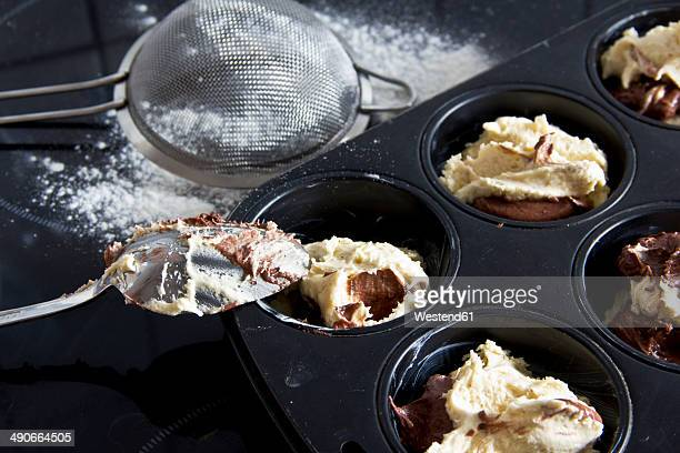 Raw muffin dough in muffin tray, spoon and strainer, close-up