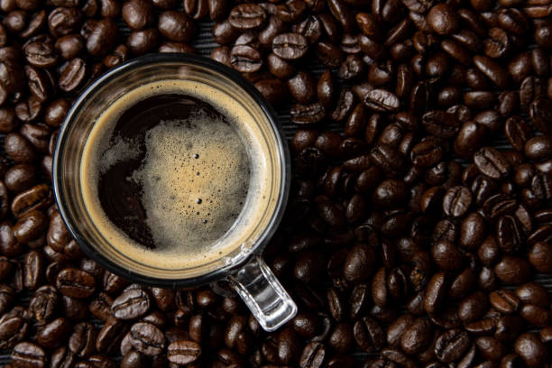 Raw organic Arabica variety coffee beans and a glass espresso cup on a cafe bean full image background. Amsterdam, The Netherlands on December 30,...