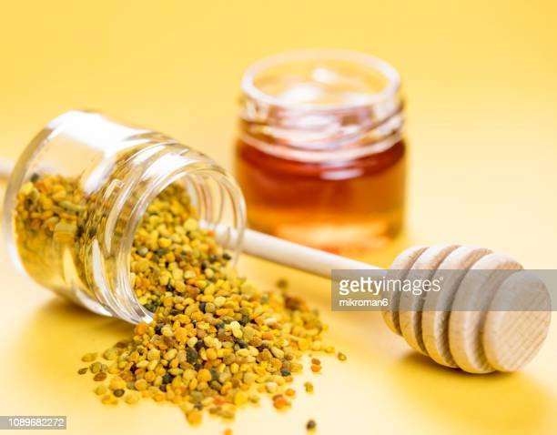 raw organic bee pollen and honey in jar. bee pollen granules. apitherapy - impollinazione foto e immagini stock