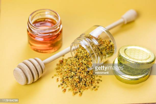 Raw organic bee pollen and honey in jar. Bee pollen granules. Apitherapy