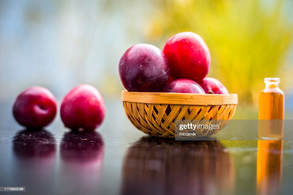 Raw organic red ripe plums in a brown-colored basket on the wooden surface along with its extracted essential oil in a small transparent bottle with blurred background. : Stock Photo