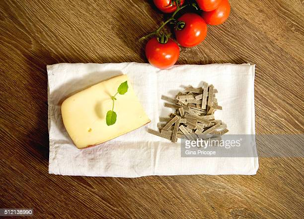 Raw pasta, cheese and tomatoes, italian food.
