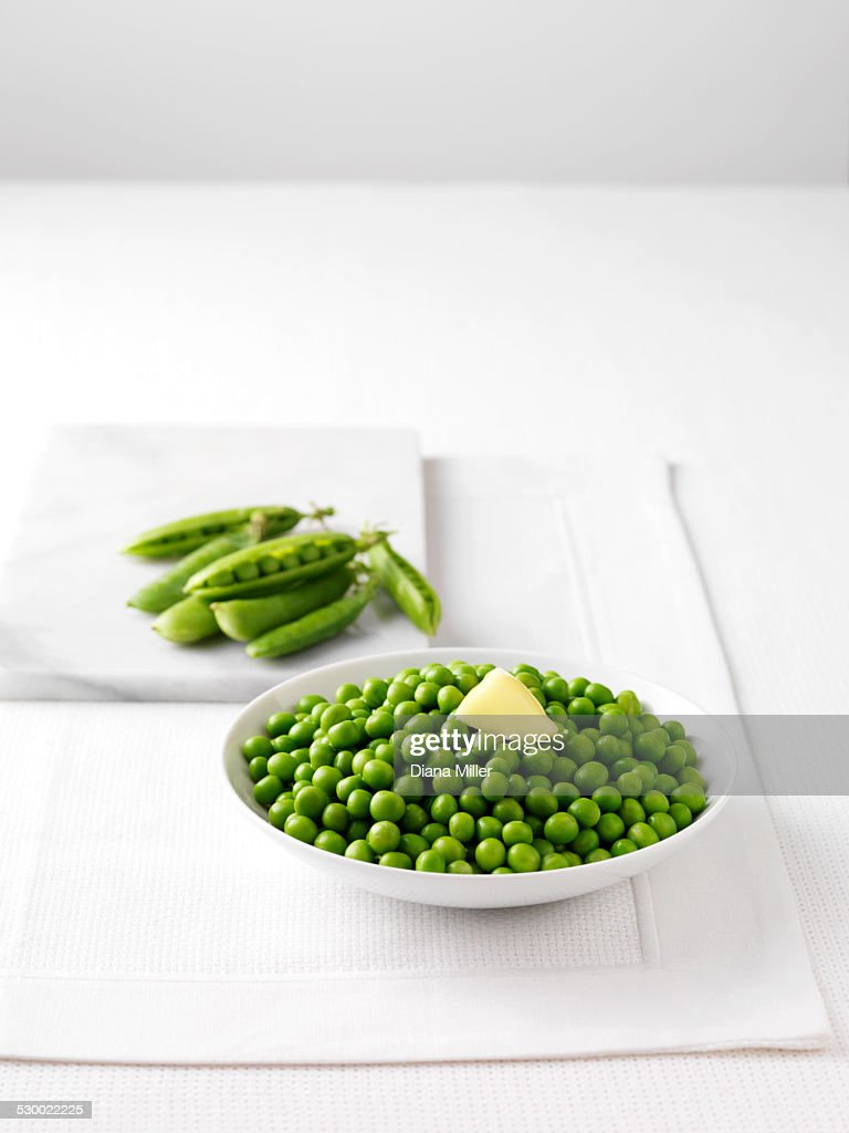 Raw pea pods on marble cutting board and bowl of boiled peas with butter : Stock Photo