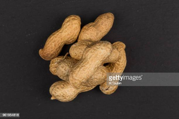 raw peanuts shells over dark stone background - peanuts stockfoto's en -beelden