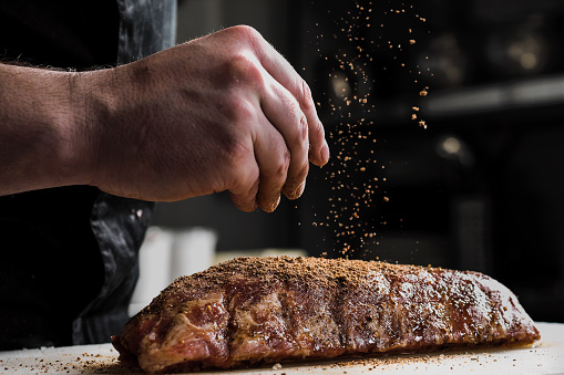 Raw piece of meat, beef ribs. The hand of a male chef puts salt and spices on a dark background. 1130934658